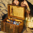 Girl on the beach with a chest of treasures — Stock Photo