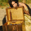 Girl on the beach with a chest of treasures — Stock Photo #9596484