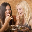 Two girls eating cake in bed — Stock Photo #9596485