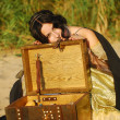 Girl on the beach with a chest of treasures — Stock Photo #9596492