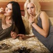 Two girls eating cake in bed — Stock Photo