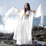 Beautiful bride posing on the coast with angelic lighting — Stock Photo