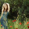 Beautiful girl on a green meadow with poppies — Stock Photo