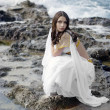 Beautiful bride posing on the coast with angelic lighting — Stock Photo