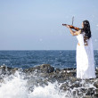 Young attractive woman playing violin on sea background — Stock Photo