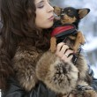 Outdoor portrait of young beautiful woman - holding her little dog in her arms — Stock Photo