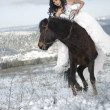 Bride with horse in snow - Stock Photo