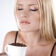 Beautiful young girl is holding a big white cup with coffee grains — Stock Photo #9599677
