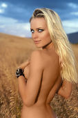 Beautiful naked woman standing in wheat field — Stock Photo