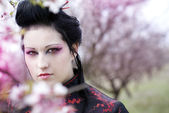 Artistic portrait of japan geisha woman with creative make-up near sakura tree in kimono — Stock Photo