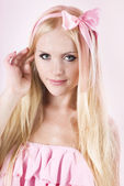 Beautiful girl in pink with a ribbon — Stock Photo
