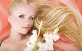Cute tiny blonde with flower in her hair — Stock Photo