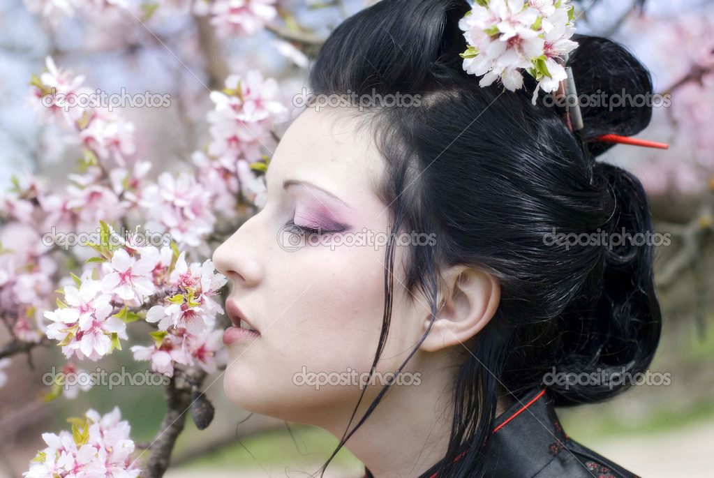 Artistic portrait of japan geisha woman with creative make-up near sakura tree in kimono   Stock Photo #9596178