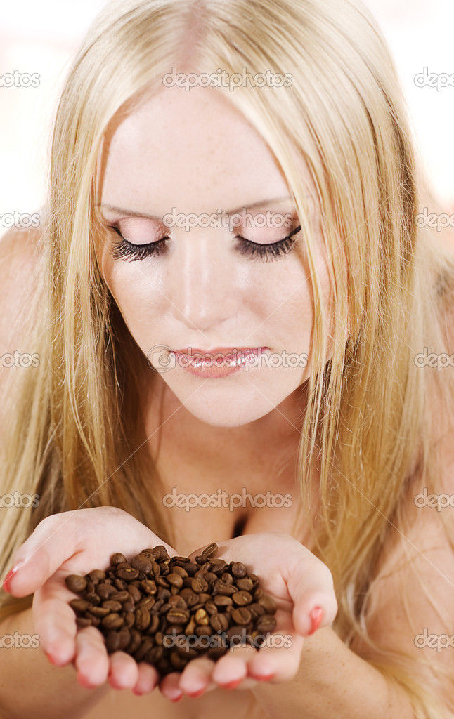 Beautiful girl holds a handful of grains coffee. — Stock Photo #9599704