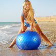Young attractive woman in sportswear doing fitness exercises with pilates gym ball on sea beach - Stock Photo