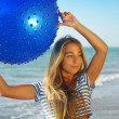 Young attractive woman in sportswear doing fitness exercises with pilates gym ball on sea beach — Stock Photo