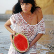 Sexy girl is sitting in the sea and holding a watermelon — Stock Photo