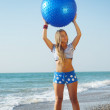 Young attractive woman in sportswear doing fitness exercises with pilates gym ball on sea beach — Stock Photo #9723612