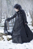 Beautiful gothic girl in the snow — Stock Photo