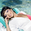 Beautiful woman relaxing on the beach lying on sunbed — Stock Photo #9740813