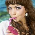 Beautiful girl in a bikini on the beach drinking juice — Stock Photo #9740835