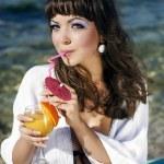 Beautiful girl in a bikini on the beach drinking juice — Stock Photo #9740841