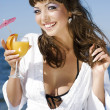 Beautiful girl in a bikini on the beach drinking juice — Stock Photo #9740851