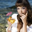 Beautiful girl in a bikini on the beach drinking juice — Стоковая фотография