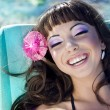 Beautiful woman relaxing on the beach lying on sunbed — ストック写真