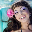 Beautiful woman relaxing on the beach lying on sunbed — Stock Photo