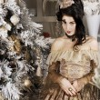 Portrait of the elegant woman posing with Christmas tree over vintage background. — Stock Photo