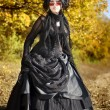 Shot of a gothic woman in a autumn park. Fashion. — Stock Photo
