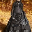 Shot of a gothic woman in a autumn park. Fashion. - Stock Photo