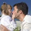 Adorable little toddler gives a sweet kiss on the nose of her father - Stock Photo