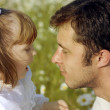 Adorable little toddler gives a sweet kiss on the nose of her father — Stock Photo #9850417