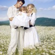 Young happy couple at the sunny day in a field with camomiles - Stock Photo