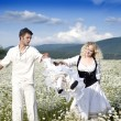 Young happy couple at the sunny day in a field with camomiles — Stock Photo #9850428