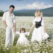 Young happy couple at the sunny day in a field with camomiles — Stock Photo