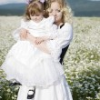 Mother and daughter at the sunny day in a field with camomiles — Stock Photo