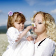 Mother and daughter at the sunny day in a field with camomiles — Stock Photo #9850438