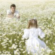 Father and daughter playing in the camomile field — Stok fotoğraf