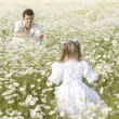 Father and daughter playing in the camomile field — 图库照片