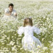 Father and daughter playing in the camomile field - Stock Photo