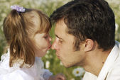 Adorable little toddler gives a sweet kiss on the nose of her father — Стоковое фото