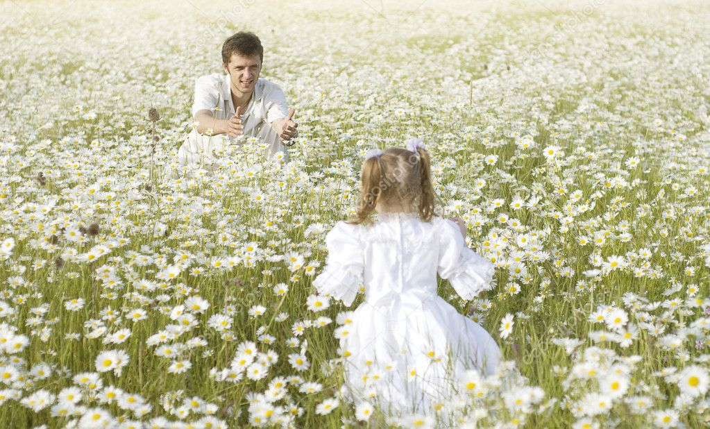 Father and daughter playing in the camomile field  Stock Photo #9850498
