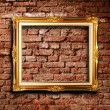 Golden frame against grunge brick wall — Stock Photo