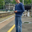 Youth texting at railway station — Stock Photo