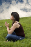 Woman sitting on grass praying — Stock Photo
