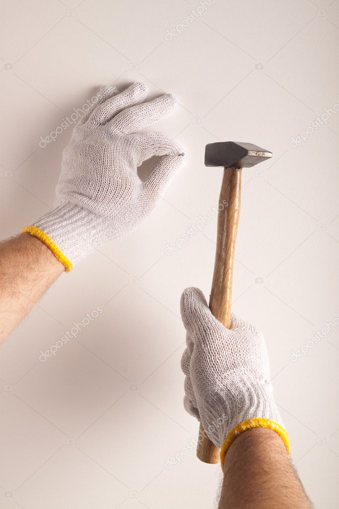 Hammering a nail into the white wall — Stock Photo #9232469