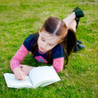 A little girl reading on the grass - from above — Stock Photo